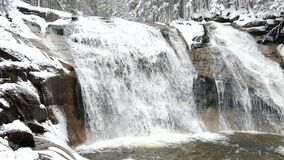 Winter waterfall.  Small pond and snowy boulders bellow cascade of waterfall. Crystal freeze water of mountain river and sounds. stock video footage