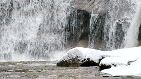 Winter waterfall. Small pond and snowy boulders bellow cascade of waterfall. Crystal freeze water of mountain river and sounds of stock footage
