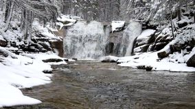 Winter waterfall.  Small pond and snowy boulders bellow cascade of waterfall. Crystal freeze water of mountain river and sounds. stock footage
