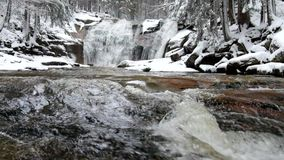 Winter waterfall.  Small pond and snowy boulders bellow cascade of waterfall. Crystal freeze water of mountain river and sounds. stock video
