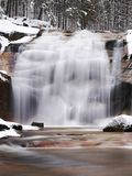 Winter waterfall. Small pond and snowy boulders bellow cascade of waterfall. Crystal freeze water of mountain river and sounds of Royalty Free Stock Photos