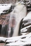 Winter waterfall. Small pond and snowy boulders bellow cascade of waterfall. Crystal freeze water of mountain river and sounds of Royalty Free Stock Images