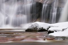 Winter waterfall.  Small pond and snowy boulders bellow cascade of waterfall. Crystal freeze water of mountain river and sounds. Stock Image