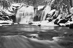 Winter waterfall. Small pond and snowy boulders bellow cascade of waterfall. Crystal freeze water of mountain river and sounds of Stock Photo