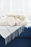 Winter Wear. Stack of winter wear and accessorize closeup on couch Royalty Free Stock Image