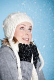 Winter weather. Happy blond girl warmly wrapped up looking up at the snow Stock Photo