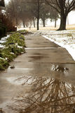 Winter weather. Rain and snow on the sidewalk. Royalty Free Stock Photos