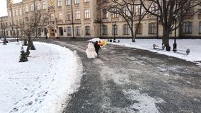 Winter wedding. Aerial view, newlywed couple in wedding dresses are runing with colorful balloons through the snow stock video footage