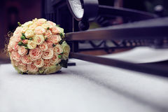 Winter wedding bouquet lying on snow. Outdoor winter close-up of wedding bouquet lying on snow near metal forged fence Stock Photos