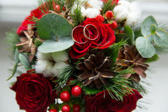 Winter wedding bouquet of red roses with wedding rings. Winter wedding bouquet of red roses with wedding rings Stock Photo