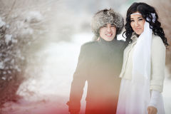 Winter wedding, exotic Asian couple newlyweds, groom in fur hat, bride wearing winter coat. Royalty Free Stock Photography
