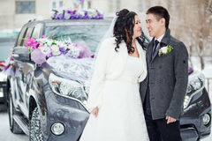 Winter wedding, the happy couple before the decorated car on a snowy street. Bride and groom look at each other. stock images