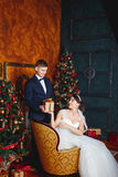 Winter Wedding .Lovers bride and groom in christmas decoration . Groom holding  Gift . romantic surprise for Christmas Stock Images