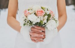 Winter wedding photo. bridal bouquet in the hands of the bride. close-up. bouquet of pink roses royalty free stock images