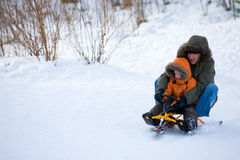 Winter weekend. Father and son sledging on beautiful winter day royalty free stock photo