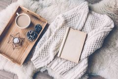 Winter weekend concept. Mug with coffee and home decor on wooden serving tray on sheep skin rug. Warm sweater and open book, winter weekend concept, top view stock photos