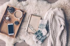 Winter weekend concept. Mug with coffee, smart phone and home decor on wooden serving tray on sheep skin rug. Warm sweater, woolen socks and open book, winter royalty free stock photos