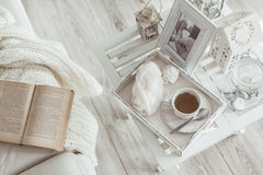 Winter weekend. Still life details, cup of tea on retro vintage wooden tray on a coffee table in living room, top view point. Lazy winter weekend with a book on Stock Photography