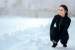 Winter-weiblicher Läufer, der zwischen den Herz Sitzungen binden ihre Schuhe stillsteht stockfotografie