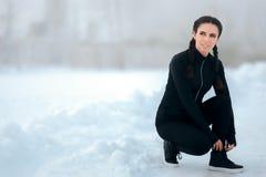 Winter-weiblicher Läufer, der zwischen den Herz Sitzungen binden ihre Schuhe stillsteht stockbild