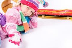 Winter: Wenig Schlitten-Mädchen mit Handvoll Schnee Lizenzfreie Stockfotografie