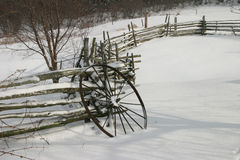 Winter Wheel II. An old iron wagon wheel leaning against a wood split-rail fence, covered in snow Royalty Free Stock Photo