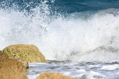 Good Timing as Wave Breaks Just before Smashing the Rocks of Boca Raton Beach. The Winter Wind brings plenty of opportunity to see the bigger waves come into royalty free stock photography