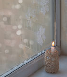 Winter window with burning candle Stock Photography