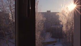 Winter window view, amazing sunbeams, cityscape, sunset stock footage