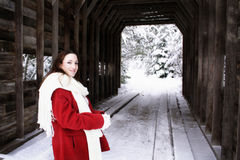 Winter Woman. Woman in red coat stands in front of a covered bridge Royalty Free Stock Photography
