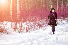 Winter woman on background of winter landscape, sun. Fashion gir Stock Images