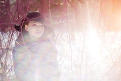 Winter woman on background of winter landscape, sun. Fashion girl in forest wonderland. Winter sunset scene. Model in sunlight, b. Acklight stock photo