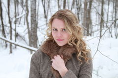 Winter Woman Beauty in Fur Trimmed Jacket. Portrait of a smiling, wholesome, beautiful young woman wearing a fur jacket in a snowy forest Royalty Free Stock Images