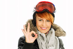 Winter woman in black jacket, helmet and goggles with fingers and sign OK Stock Photos