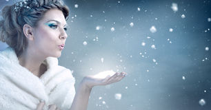 Winter woman blowing snow - snow queen. Winter woman blowing snow over blue background - snow queen Stock Photos