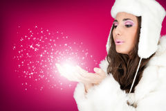 Winter woman blowing snowflakes. Beautiful winter woman blowing snowflakes from her hands Stock Photos