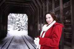 Winter Woman on Bridge. Smiling woman in red coat in front of a covered bridge Royalty Free Stock Image