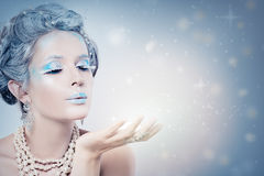 Winter Woman Fashion Model Blowing Snow at Night. Snow Queen Girl on Blue Background with Stars, Snow and Glitters Royalty Free Stock Photo