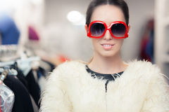 Winter Woman in Fur Coat with Big Sunglasses. Fabulous diva in fashion store wearing oversized glasses and fur jacket Stock Photography