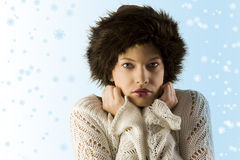 Winter woman with fur hat. Portrait of nice winter woman with white sweater and brown fur hat on sky blue background Royalty Free Stock Photography