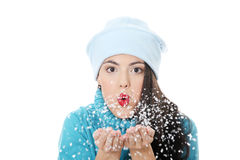 Winter woman in hat blowing on snow. Royalty Free Stock Photography