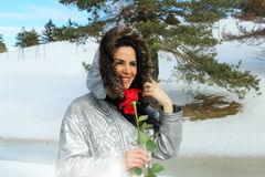Winter woman holding red rose. Portrait of a beautiful, Caucasian woman, holding red rose in a winter background. Winter leisure scene Royalty Free Stock Images