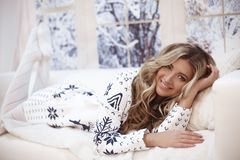 Winter woman indoor portrait. Young beautiful blond girl in warm knitted clothes by snow window at home. Fashion style cloth stock photography