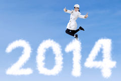 Winter woman jumps over new year 2014 Royalty Free Stock Photography