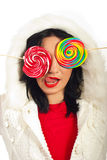 Winter woman loving lollipop. Winter woman  in white wool pullover with fur hood covering eyes with colorful lollipops and liking her lips against white Stock Images