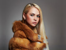 Winter Woman in Luxury Fur Coat. Beauty Fashion Model Girl. Beautiful stylish blond girl Healthy hair Royalty Free Stock Images