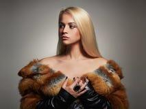 Winter Woman in Luxury Fur Coat. Beauty Fashion Model Girl. Beautiful stylish blond girl Healthy hair Stock Image