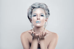 Winter Woman Model with Snow Glitters Makeup Blowing a Kiss Stock Photography