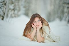 Winter woman portrait lying on the snow Stock Photos