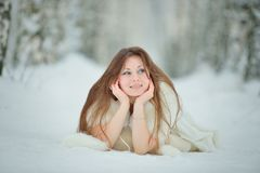 Winter woman portrait lying on the snow Royalty Free Stock Image